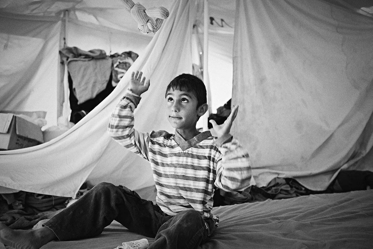 The dismal paraphernalia of refugee living surrounds this child though he and his 'friend' are oblivious to them, and indeed to the camera. He has entered into his own world.