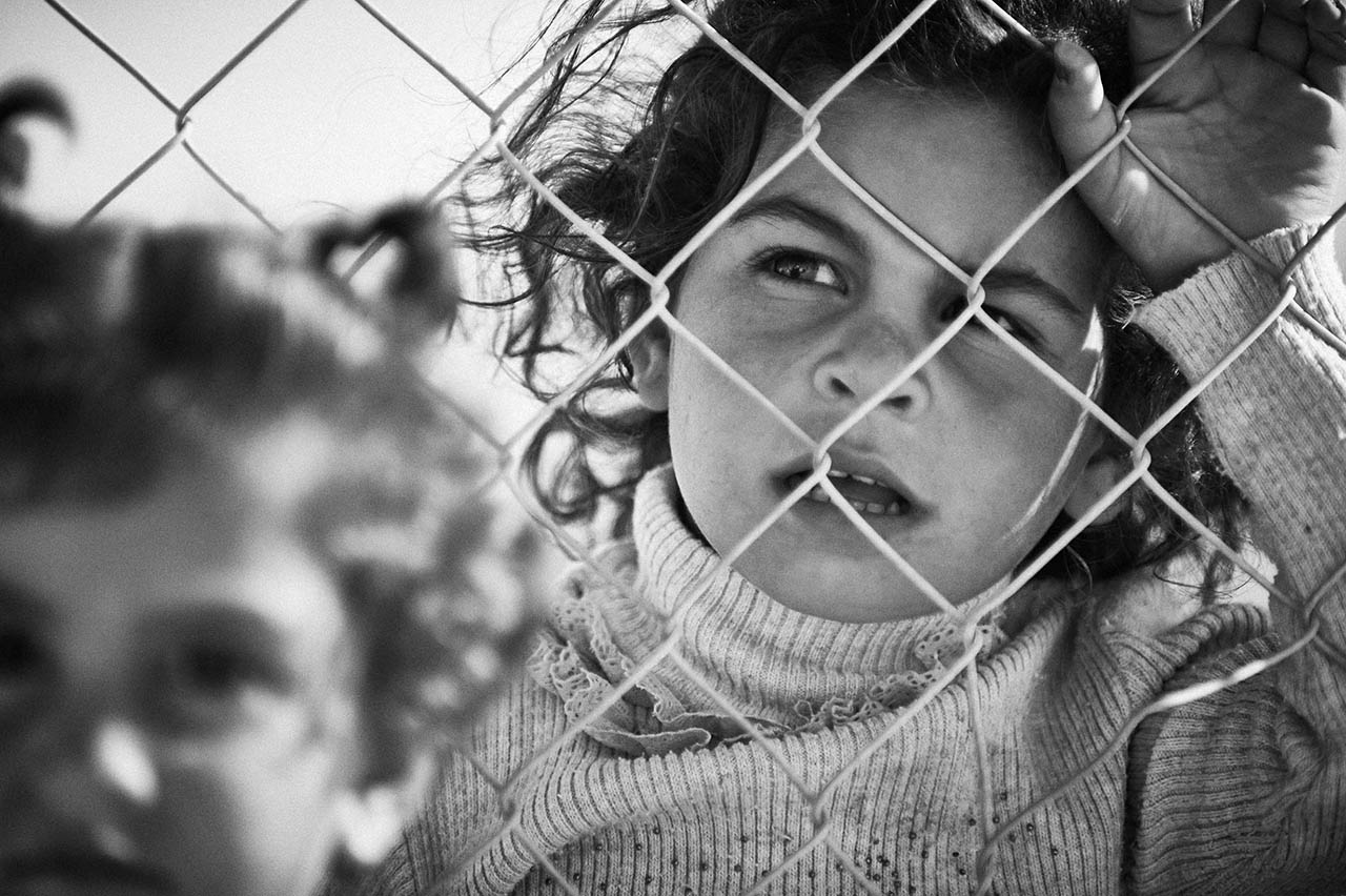 I am not sure whether a young girl should have such a grown up expression or a face that asks so many questions. It is as if the ghost-like image of the girl in the foreground, not quite one side of the fence nor the other, is her soul fleeing or fading.