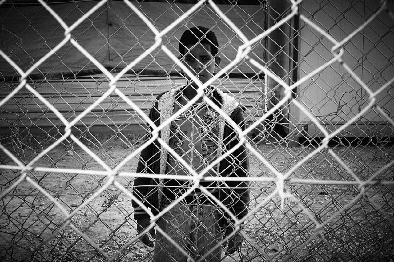 There is nothing so un-nerving to the photographer as light bouncing back to his camera. It is a symbolic failure. Even if all the layers of fencing were cut away and the young man was able to stand there clearly lit, he is still a thousand miles away from you and I.